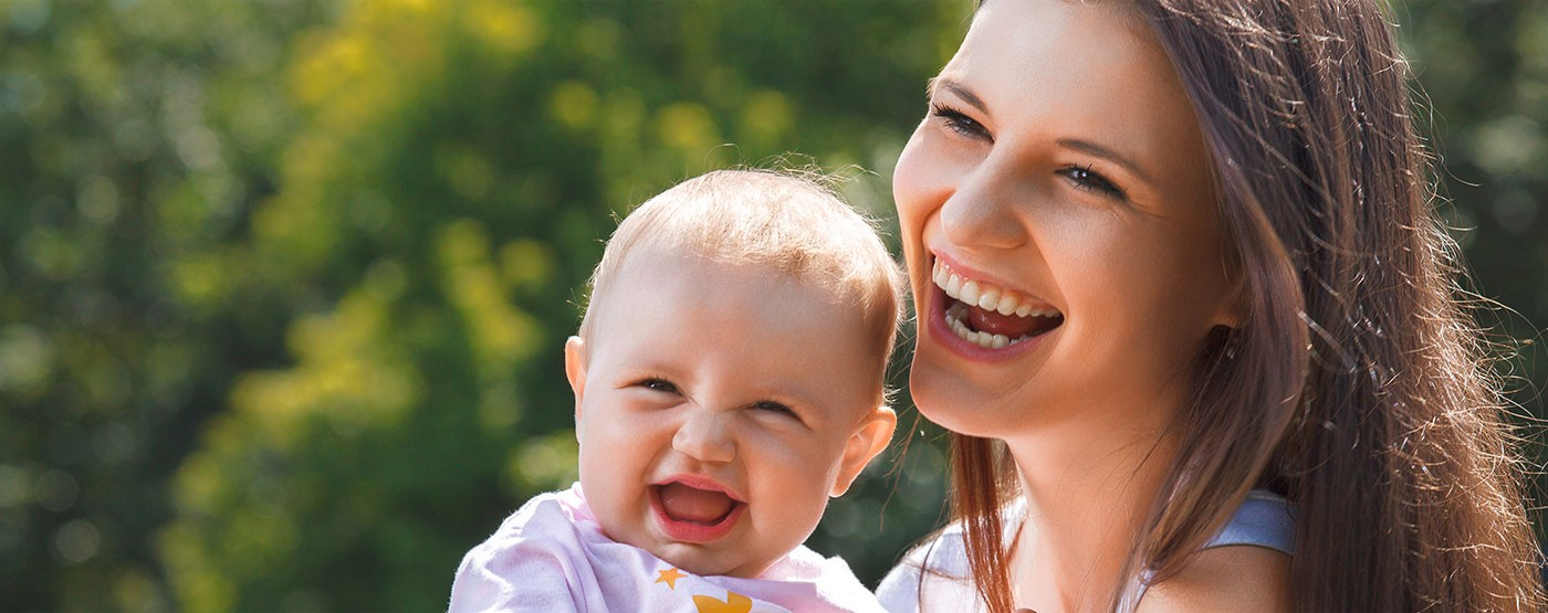 Woman smiling with her about about the Jogalong Jogging Stroller